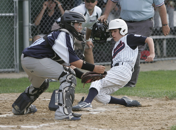 Lynn:  Swampscott's Jack Morrett, right, slides home safe past    Peabody American catcher Alex Gomes. photo by Mark Teiwes / Salem News