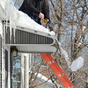 Beverly:  Justin Gadd of Cicoria Tree and Crane Service clears a ice dam from a clients house using a chisel, shovel, hammer, and ladder.  photo by Mark Teiwes  / Salem News