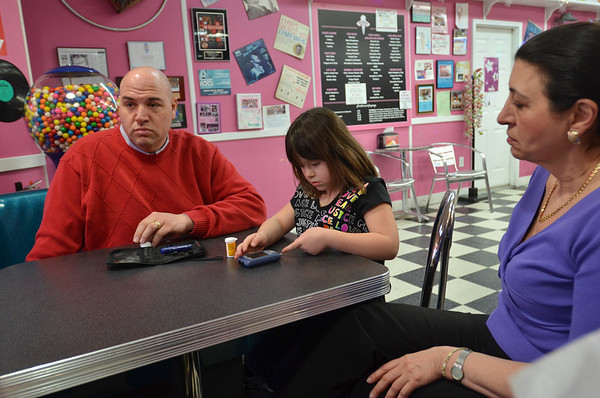 Danvers: Wylinn Palmisano, 6, tests her blood sugar with her father John, the owner of Goodies Ice Cream, and grandmother Terry.    photo by Mark Teiwes / Salem News