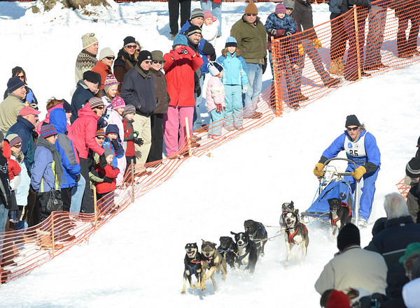 Ipswich: A crowd lines the start of the Myopia Sled Dog Race as Doug Butler comes flying down a hill with his team of eight dogs.  photo by Mark Teiwes  / Salem News
