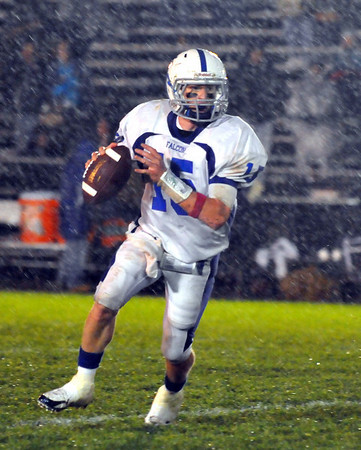 Beverly:  Danvers quarterback Greg Little looks for a pass as the rain comes down Friday night. photo by Mark Teiwes / Salem News