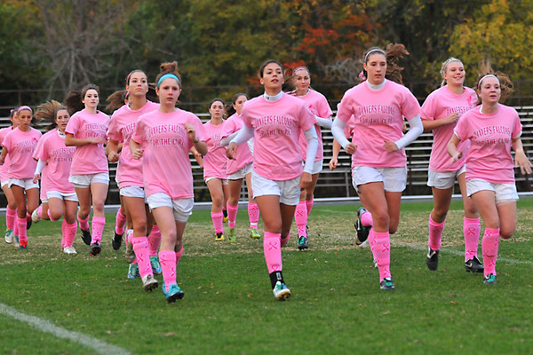 "Danvers: Danvers girls soccer team wear pink socks and pink shirts saying ""Danvers Falcons for the Cure"" during warmups to promote breast cancer awareness.   photo by Mark Teiwes / Salem News"
