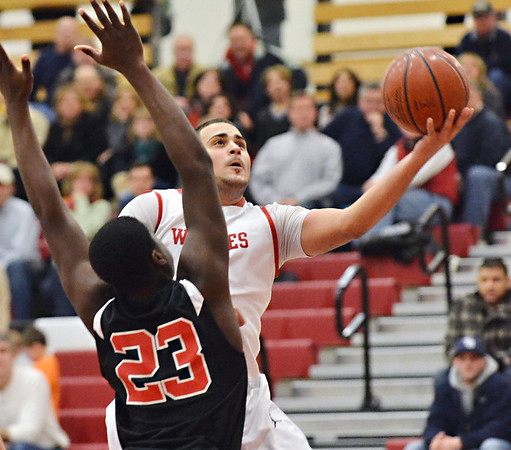 Salem: Salem High School guard Antonio Reyes flies to the hoop past Marblehead's Malik Abu to make a key layup in the last minutes of Salem's 71-70 overtime win. photo by Mark Teiwes / Salem News
