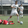 Beverly: Endicott soccer player Jed Magnusson eludes a slide tackle by Bridgewater State's Donald Flores.  photo by Mark Teiwes  / Salem News