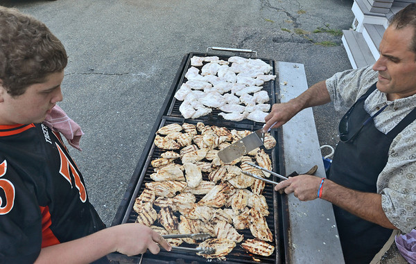 Ipswich: Mike Dillon of Ipswich, 16, left, grills 200 chicken breasts for the night's meal with Dinner Bell volunteer Drew Nikas of Ipswich.  photo by Mark Teiwes /  Salem News