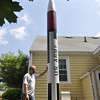 Salem: Robert DeHate, an amateur rocket enthusiast stands in his backyard next to his 17-foot rocket which will be shot up more than a mile at an event in California next month with a friend's ashes inside. photo by Mark Teiwes / Salem News