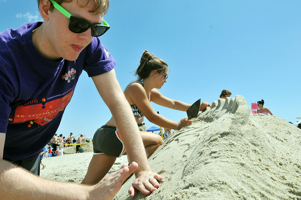 "Ipswich: David Moffat, left, of Salem and Corey Goodwin of Hamilton work on a sculpture entitled ""Dragon Snacks"" featuring two dragons eating each other's tails.  The sculpture went on to win its business/organization category, the people's choice, and the judges choice at the Crane Beach Sand Blast.  photo by Mark Teiwes / Salem News"