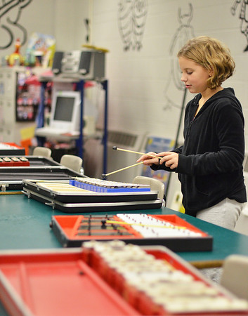 """Salem: Fifth grader Olivia Leger played the song """"Hot Cross Buns"""" on metallophones, xylophones, and marimbas in Mrs. Anderson music classroom for the Collins Middle School open house.  photo by Mark Teiwes / Salem News"""