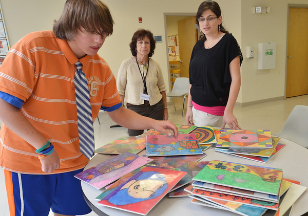 "Danvers: Cameron ""C.J."" Mercier of Danvers, 19, looks through his art with Suzanne Ryan of the Northeast Arc and his personal care attendant Becca Hartman, right.   photo by Mark Teiwes  / Salem News"