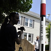 Salem: Keith Gaillard, left, takes video to send to the Discovery Channel of Robert DeHate, an amateur rocket enthusiast, standing in his backyard next to his 17-foot rocket which will be shot up more than a mile at an event in California next month with a friend's ashes inside. photo by Mark Teiwes / Salem News