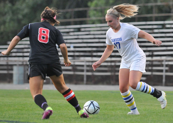 Danvers: Danvers striker Corey Persson, right, looks to the goal defended by North Andover's Rachel Barnes. photo by Mark Teiwes / Salem News