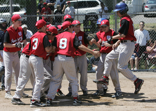 Danvers: Amesbury's Jerod Lawther, right, leaps onto heme plate after hitting a homerun in a District 15 Little League all-star game against Hamilton-Wenham.   photo by Mark Teiwes / Salem News