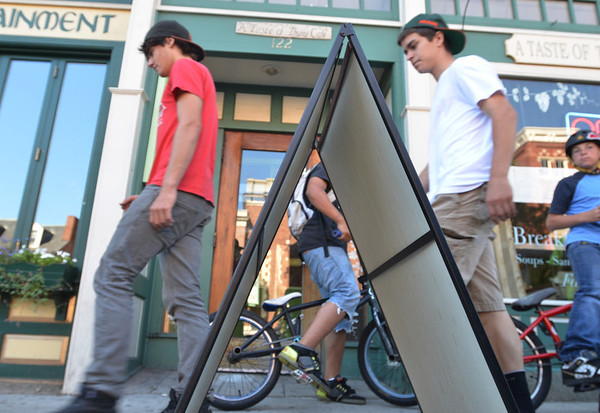 Salem:  Cameron Darmody of Salem, left, and Connor O'Leary of Marblehead walk past A Taste of Thyme Cafe's A-frame sign at on Washington Street.   photo by Mark Teiwes /  Salem News