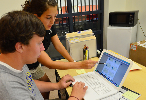 "Beverly: Charla Bouranis, right, licensed athletic trainer, goes over the baseline ""Impact Test"" results with soccer player Carl Zeroka.  If an athlete has a concussion, the test is taken again. The results then are compared with preseason figures.      photo by Mark Teiwes / Salem News"