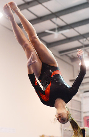 Middleton: Masconomet gymnast performs a spinning flip off the beam.   photo by Mark Teiwes  / Salem News