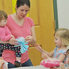 Hamilton:  Katie Logemann of Wenham works on making paper flowers with her daughters Grace, 1, left, Emily, 2, and Megan, 2, for a Mother's Day event at the Hamilton-Wenham Public Library.  Mark Teiwes / Salem News