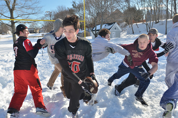 Marblehead:  A group of Marblehead High School football players gathered on Superbowl Sunday at Gatchell playground for some snow football.  Michael Asaiante, center, makes a touchdown scoring play.  photo by Mark Teiwes  / Salem News