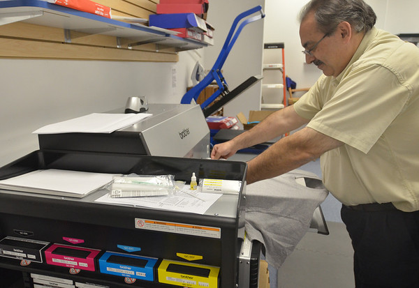 Middleton:  Sarkis Sarkisian prepares a shirt to be printed on a garment printer.  photo by Mark Teiwes / Salem News.