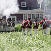 Marblehead: Glover's Regiment, left, exchange blank shots with British soldiers.  Actors recreate 1775 military encampment and mock battles in Marblehead. photo by Mark Teiwes / Salem News