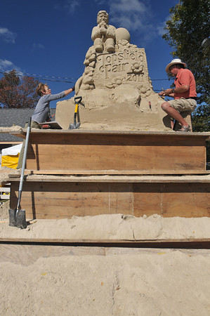Topsfield: Kristie Haupt, left, and Justin Gordon of Elwin Designs craft a 15 ft tall sand sculture at the Topsfield Fair.   photo by Mark Teiwes / Salem News