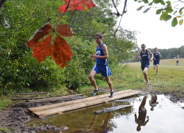 Topsfield:   Danvers runner Brian Herbert leads the pack across a puddle and later finished second in the race. photo by Mark Teiwes / Salem News