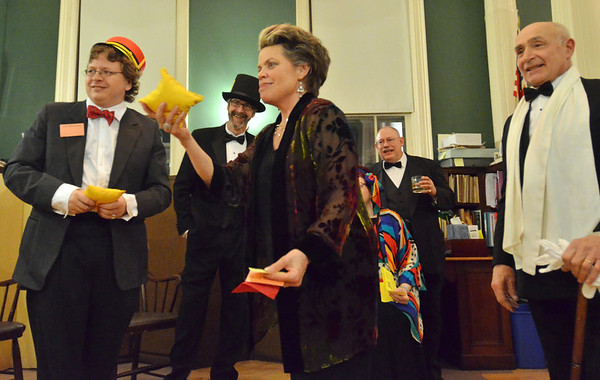 Salem:  The Salem Athenaeum hosted a Monopoly themed party.  Francie King, center, plays a bean bag toss game watched by Joe McGuire, left, Timothy Lutts, Walter Lederhaus and Bob Erbetta, right.   Monopoly was manufactured by Parker Brothers in Salem starting in 1935. photo by Mark Teiwes