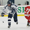 Wilmington: St. John's Prep forward Colin Blackwell flicks the puck eluding Hingham's Tyler Mahoney.  Blackwell scored the fourth goal in the team's 4-4 tie against Hingham. photo by Mark Teiwes  / Salem News