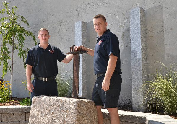 Salem: Salem Firefighters Tom Brophy, left, and Manny Ataide hold a steel I-beam from the World Trade Center in New York.  The piece is part of a new 9/11 memorial outside the downtown Salem Fire Department that will be finished for its dedication on September 11th.  photo by Mark Teiwes /  Salem News