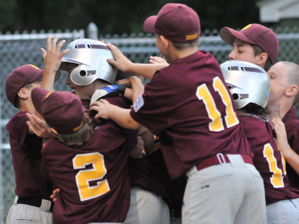 Beverly: Danvers National little league players celebrate with Jack Anderson after he hit a home run. photo by Mark Teiwes  / Salem News