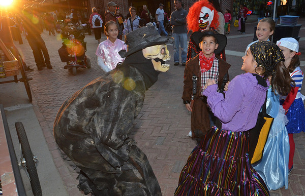 Salem: The Nightmare Factory's Douglas Merrill, left, suprises Jenna Tremblay, 9, of Salem along Essex Street during the Mayor's Night Out trick-or-treat.  photo by Mark Teiwes / Salem News