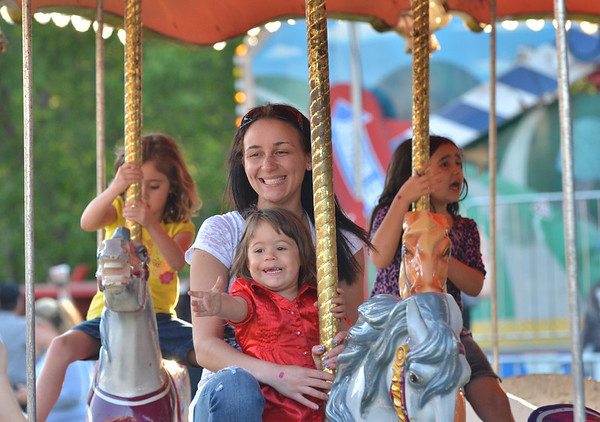 Beverly:  Nicole Dove of Beverly rides with Neveah Deleon, 2, on a merry-go-round.  The carnival runs through Sunday with proceeds to benefit to the Beverly Education Foundation.  photo by Mark Teiwes / Salem News