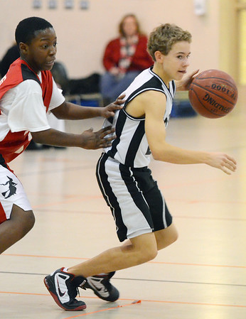 Ipswich: Ipswich 8th grade travel basketball player Mike Savaie dribbles from Salem's Keyshaun Jacobs.  photo by Mark Teiwes  / Salem News