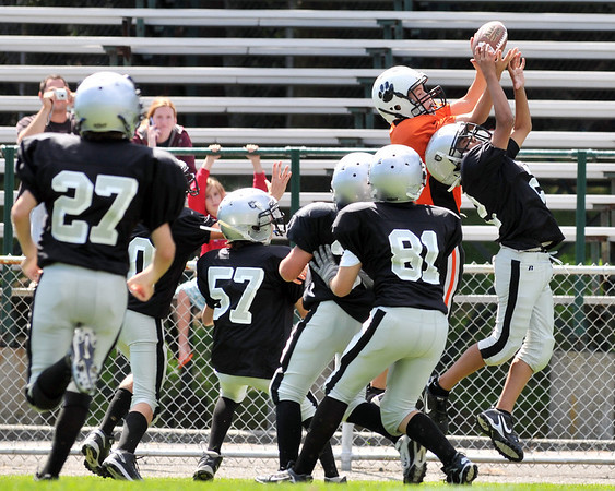 Beverly: Beverly Black receiver Jordon Rawding makes a jumping catch surrounded by Peabody Raiders defenders.   Beverly beat Peabody 14-0. photo by Mark Teiwes / Salem News