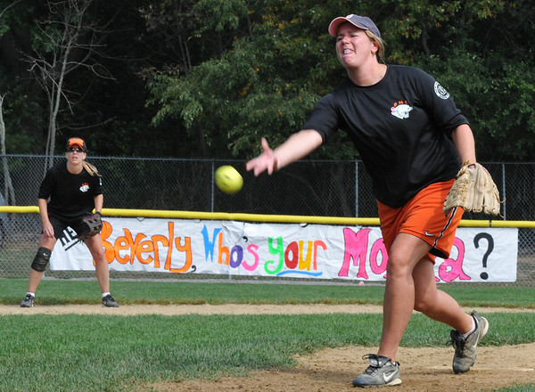 """Beverly: At the 11th annual Momball softball tournament, Anne Flaherty releases a pitch, playing on a team made from moms of students at Beverly High School   The sign behind her reads, """"Hey Bevery, who's your Mamma?""""  photo by Mark Teiwes / Salem News"""