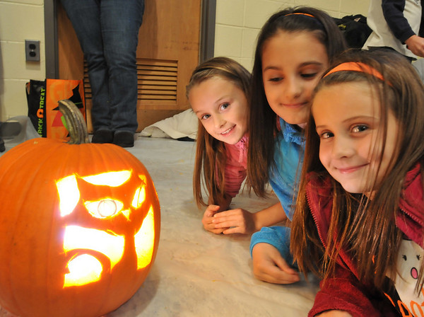 Middleton:  Sisters Isabel Bruce, left, 6, Emma, 9 and Lily, 8, pose next to their cat faced pumpkin carving.  photo by Mark Teiwes / Salem News