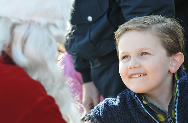 Danvers: 5-year-old Ryan Mcfadden of Beverly looks up at Santa after he arrived at Pope's Landing.  photo by Mark Teiwes / Salem News