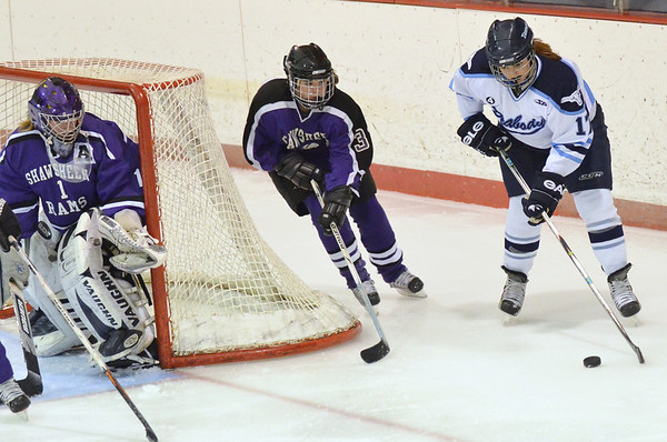 Peabody: Peabody girls hockey player Lauren White, right wraps around the goal for a shot on Shawsheen Tech goalie Jen Curtis, left.   photo by Mark Teiwes  / Salem News