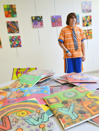 "Danvers: Cameron ""C.J."" Mercier of Danvers, 19, stands before his art show at the Northeast Arc. He has progressed tremendously since suffering brain damage in a 2006 accident.   photo by Mark Teiwes  / Salem News"