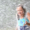 Wenham: Tess Contois of Wenham, 9, runs through a spray of water after being covered with foam during a summer program run by the Wenham Village Improvement Society. photo by Mark Teiwes / Salem News.