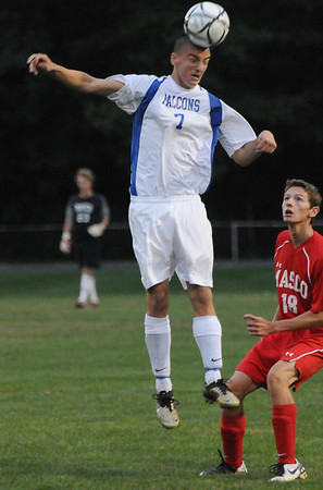 Danvers: Danvers forward Jon Amico wins a header watched by Masconomet's Justin Clark.  photo by Mark Teiwes / Salem News