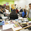 Salem: Eighth grader Uliana Certan, right, stands beside a table of books that have been banned by various schools and cities.  Eighth grade teacher Teague Desmond reads a passage from the Lord of the Rings front of the class which was banned because it contains elements that are supernatural and anti-religious. photo by Mark Teiwes / Salem News