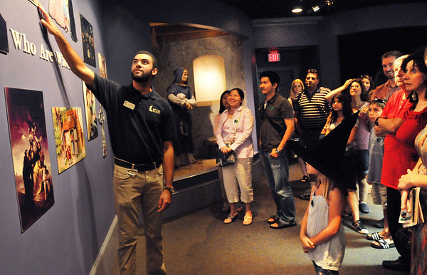 Salem: Salem has had a busy summer tourism season.  Aarin Fouhey of Salem leads tourists through a exhibit at the Witch Museum.   &-year-old Jayden Hart, right, of Haverhill wears a witches hat during the tour.  photo by Mark Teiwes / Salem News