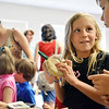 Swampscott: Izabella Pitman of Swampscott, 8 shows her brother Ted, 10, an ammonite fossil at the start of a dinosaurs and fossils program at the Swampscott Public Library.  photo by Mark Teiwes / Salem News