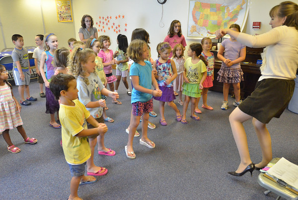 Salem: Librarian Courtney Davis, right, starts off the Salem Public Library children's program leading the kids in a song and dance. photo by Mark Teiwes /  Salem News