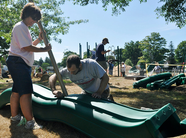 Beverly: Dierdre Patch, left, and Brian Chirco, members of the Friends of Cove Park group, put together a slide for the new playground.  photo by Mark Teiwes / Salem News