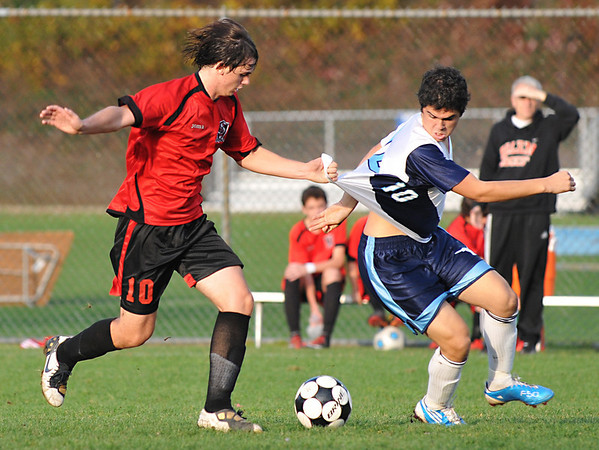 Peabody:  Peabody's Nicholas Melo, left, yanks the shirt of Salem's Brion Likaj.  photo by Mark Teiwes / Salem News