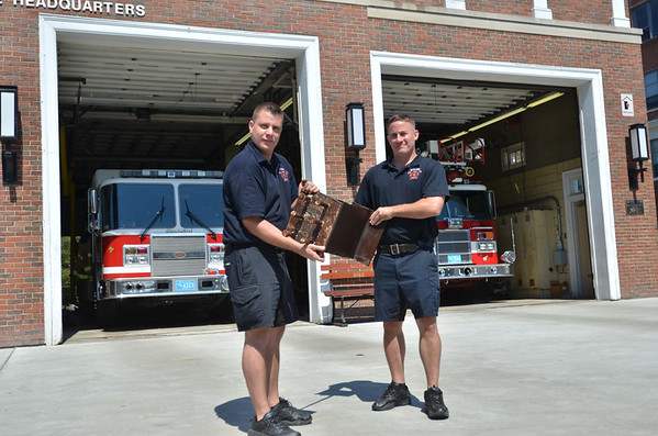 Salem: Salem Firefighters Manny Ataide, left, and Tom Brophy hold a steel I-beam from the World Trade Center in New York.  The piece is part of a 9/11 memorial outside the downtown Salem Fire Department that will be finished for its dedication on September 11th.  photo by Mark Teiwes /  Salem News