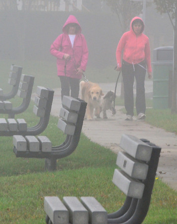 Beverly: Patty Grondin, left, and Susan Dumas, both from Beverly, walk with their dogs Frank and Teddy past Independence Park in the mist and fog yesterday afternoon.  photo by Mark Teiwes / Salem News