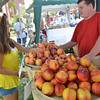 Peabody: Francesca Patania of Peabody, 15, purchases some fruit from Nick Srybny with the Hereford Valley Farm in Andover during a farmers' market at the Peabody Institute Library.  photo by Mark Teiwes /  Salem News