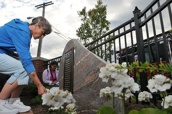Beverly: Kathie Belanger places a flower in front the memorial.   photo by Mark Teiwes / Salem News